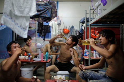 Migrant construction workers drink beer during a meal inside their dormitory after a shift at a residential construction site in Shanghai